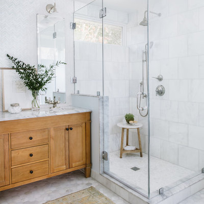 Mid-sized transitional master white tile and mosaic tile marble floor and gray floor corner shower photo in Austin with furniture-like cabinets, light wood cabinets, an undermount sink, marble countertops, a hinged shower door and white countertops