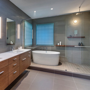 Design ideas for a mid-sized modern master bathroom in Dallas with an undermount sink, furniture-like cabinets, medium wood cabinets, recycled glass benchtops, a freestanding tub, an open shower, beige tile, porcelain tile and porcelain floors.