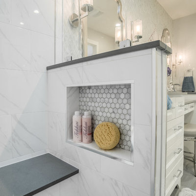 Example of a small transitional master white tile and marble tile porcelain tile and gray floor corner shower design in Dallas with shaker cabinets, white cabinets, a two-piece toilet, gray walls, an undermount sink, quartz countertops and a hinged shower door