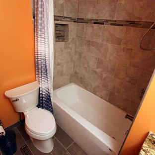 Diseño de cuarto de baño principal, tradicional, pequeño, con lavabo bajoencimera, armarios con paneles empotrados, puertas de armario de madera en tonos medios, encimera de granito, bañera empotrada, combinación de ducha y bañera, sanitario de dos piezas, baldosas y/o azulejos grises, baldosas y/o azulejos de porcelana, parades naranjas y suelo de baldosas de porcelana