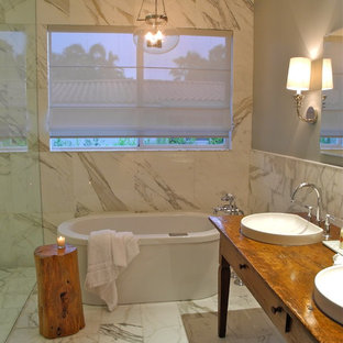 Inspiration for a contemporary white tile freestanding bathtub remodel in Miami with a vessel sink, furniture-like cabinets, medium tone wood cabinets, wood countertops and brown countertops