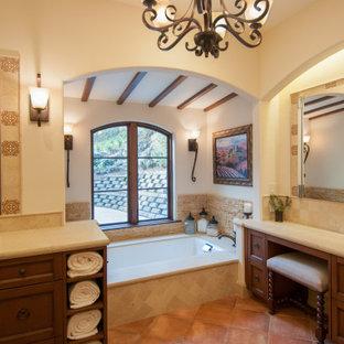 На фото: большая главная ванная комната в средиземноморском стиле с фасадами с утопленной филенкой, фасадами цвета дерева среднего тона, полновстраиваемой ванной, душем без бортиков, биде, бежевой плиткой, плиткой из известняка, бежевыми стенами, полом из керамогранита, врезной раковиной, столешницей из искусственного кварца, оранжевым полом, душем с распашными дверями, бежевой столешницей, унитазом, тумбой под две раковины, встроенной тумбой и балками на потолке