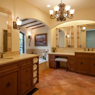 Idéer för att renovera ett stort medelhavsstil beige beige en-suite badrum, med luckor med infälld panel, skåp i mellenmörkt trä, ett undermonterat badkar, en kantlös dusch, en bidé, beige kakel, kakelplattor, beige väggar, klinkergolv i porslin, ett undermonterad handfat, bänkskiva i kvarts, orange golv och dusch med gångjärnsdörr