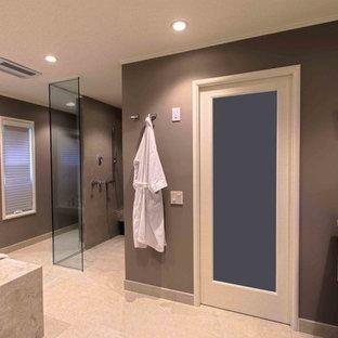 サンフランシスコの大きいコンテンポラリースタイルのおしゃれなマスターバスルーム (段差なし、一体型トイレ、茶色い壁、磁器タイルの床、フラットパネル扉のキャビネット、ベージュのキャビネット、ライムストーンの洗面台、ベージュのタイル、磁器タイル、アンダーマウント型浴槽) の写真