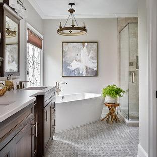 Diseño de cuarto de baño principal, tradicional renovado, de tamaño medio, con armarios con paneles con relieve, puertas de armario de madera oscura, bañera exenta, ducha esquinera, sanitario de una pieza, baldosas y/o azulejos grises, baldosas y/o azulejos en mosaico, paredes grises, suelo de mármol, lavabo bajoencimera y encimera de cuarzo compacto