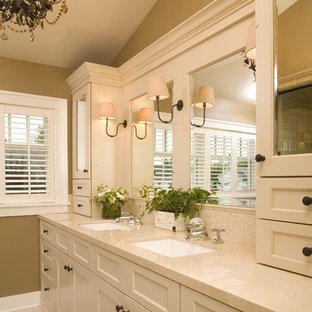 Exemple d'une salle de bain chic avec un lavabo encastré, un placard à porte shaker, des portes de placard beiges, un carrelage beige, du carrelage en travertin et un plan de toilette beige.
