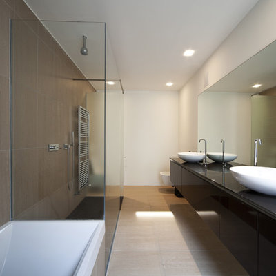 Inspiration for a large modern master stone tile slate floor bathroom remodel in Phoenix with black cabinets, white walls, a pedestal sink, flat-panel cabinets, a wall-mount toilet and glass countertops