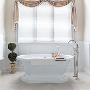 デトロイトの巨大なトラディショナルスタイルのおしゃれなマスターバスルーム (落し込みパネル扉のキャビネット、白いキャビネット、置き型浴槽、コーナー設置型シャワー、ビデ、白いタイル、磁器タイル、ベージュの壁、磁器タイルの床、アンダーカウンター洗面器、クオーツストーンの洗面台、ベージュの床、開き戸のシャワー、白い洗面カウンター、トイレ室、洗面台2つ、造り付け洗面台、三角天井、羽目板の壁) の写真