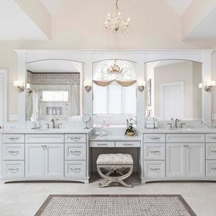 Неиссякаемый источник вдохновения для домашнего уюта: огромная главная ванная комната в классическом стиле с фасадами с утопленной филенкой, белыми фасадами, отдельно стоящей ванной, угловым душем, биде, белой плиткой, керамогранитной плиткой, бежевыми стенами, полом из керамогранита, врезной раковиной, столешницей из искусственного кварца, бежевым полом, душем с распашными дверями, белой столешницей, унитазом, тумбой под две раковины, встроенной тумбой, сводчатым потолком и панелями на стенах