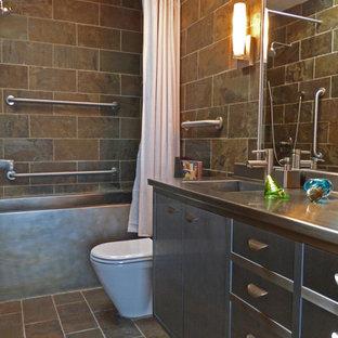 Стильный дизайн: маленькая главная ванная комната в стиле ретро с монолитной раковиной, плоскими фасадами, серыми фасадами, столешницей из нержавеющей стали, ванной в нише, душем над ванной, унитазом-моноблоком, серой плиткой, каменной плиткой, зелеными стенами и полом из сланца - последний тренд