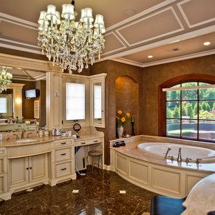 Ispirazione per una grande stanza da bagno padronale vittoriana con ante con riquadro incassato, ante beige, vasca da incasso, pareti marroni, pavimento in marmo, lavabo sottopiano, top in granito e pavimento marrone