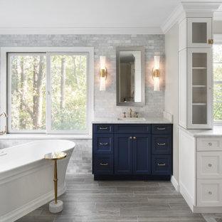 Badezimmer mit flächenbündigen Schrankfronten, blauen Schränken, freistehender Badewanne, gelben Fliesen, Marmorfliesen, Fliesen in Holzoptik, Unterbauwaschbecken, Marmor-Waschbecken/Waschtisch, grauem Boden, gelber Waschtischplatte, Einzelwaschbecken und eingebautem Waschtisch in St. Louis