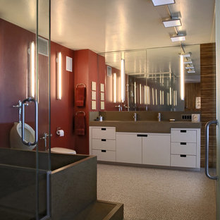 Large trendy master ceramic floor, multicolored floor, double-sink and wall paneling bathroom photo in Chicago with flat-panel cabinets, white cabinets, a wall-mount toilet, red walls, an integrated sink, concrete countertops, a hinged shower door, gray countertops and a built-in vanity