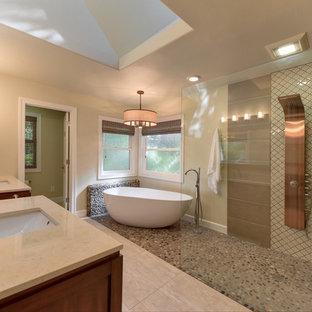 サクラメントの大きいトランジショナルスタイルのおしゃれなマスターバスルーム (フラットパネル扉のキャビネット、中間色木目調キャビネット、置き型浴槽、コーナー設置型シャワー、分離型トイレ、茶色いタイル、石タイル、ベージュの壁、スレートの床、アンダーカウンター洗面器、珪岩の洗面台、ベージュの床、オープンシャワー) の写真