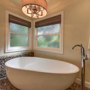 サクラメントの大きいトランジショナルスタイルのおしゃれなマスターバスルーム (フラットパネル扉のキャビネット、中間色木目調キャビネット、置き型浴槽、コーナー設置型シャワー、分離型トイレ、茶色いタイル、石タイル、ベージュの壁、アンダーカウンター洗面器、珪岩の洗面台、玉石タイル) の写真