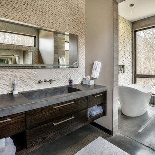 Diseño de cuarto de baño principal, actual, con armarios con paneles lisos, puertas de armario de madera en tonos medios, bañera exenta, suelo de cemento, lavabo integrado, encimera de cemento, suelo gris, baldosas y/o azulejos beige, suelo de baldosas tipo guijarro y paredes beige