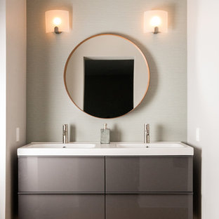 Example of a mid-sized trendy master beige tile and ceramic tile medium tone wood floor and brown floor alcove shower design in Philadelphia with flat-panel cabinets, gray walls, an integrated sink, gray cabinets, solid surface countertops and a hinged shower door