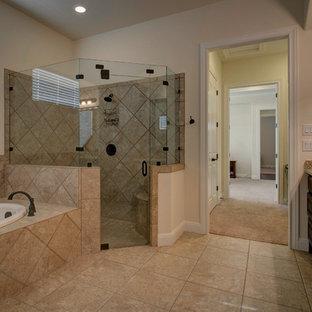 オースティンのラスティックスタイルのおしゃれな浴室 (レイズドパネル扉のキャビネット、茶色いキャビネット、ドロップイン型浴槽、コーナー設置型シャワー、ベージュのタイル、磁器タイル、白い壁、磁器タイルの床、アンダーカウンター洗面器、御影石の洗面台、ベージュの床、開き戸のシャワー、ベージュのカウンター) の写真