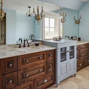 Idee per una stanza da bagno padronale tradizionale di medie dimensioni con pareti blu, pavimento in pietra calcarea, lavabo sottopiano, top in granito, pavimento beige, top beige, consolle stile comò e ante in legno bruno