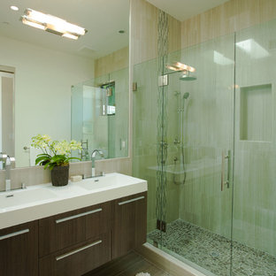 Diseño de cuarto de baño con ducha, actual, pequeño, con lavabo integrado, armarios con paneles lisos, puertas de armario de madera en tonos medios, encimera de acrílico, ducha esquinera, baldosas y/o azulejos beige, baldosas y/o azulejos de porcelana, paredes beige y suelo de baldosas de porcelana