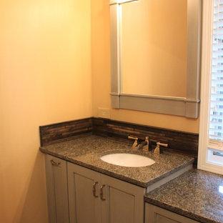 Foto di una stanza da bagno padronale tradizionale di medie dimensioni con ante grigie, doccia doppia, WC monopezzo, lavabo sottopiano, top in granito, ante con riquadro incassato, piastrelle grigie, piastrelle in ardesia, pareti gialle e pavimento in gres porcellanato