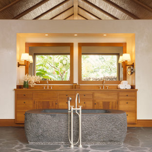 Inspiration for a tropical bathroom in San Francisco with medium wood cabinets and a freestanding tub.
