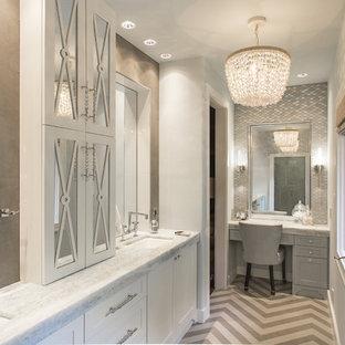 ヒューストンの大きいトランジショナルスタイルのおしゃれなマスターバスルーム (アンダーカウンター洗面器、家具調キャビネット、白いキャビネット、珪岩の洗面台、置き型浴槽、シャワー付き浴槽、壁掛け式トイレ、グレーのタイル、磁器タイル、グレーの壁、磁器タイルの床) の写真