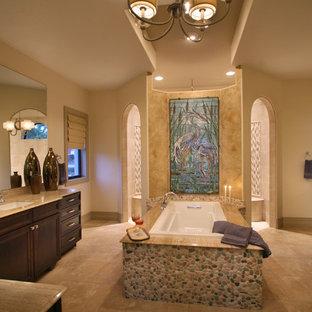 Modelo de cuarto de baño principal, exótico, grande, con armarios con paneles empotrados, puertas de armario de madera en tonos medios, encimera de granito, bañera encastrada, ducha abierta, baldosas y/o azulejos beige, suelo de baldosas tipo guijarro, paredes beige, suelo de travertino, suelo beige, ducha abierta y encimeras beige