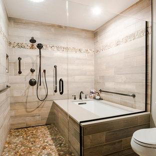 Modelo de cuarto de baño principal, actual, de tamaño medio, con puertas de armario de madera clara, bañera esquinera, combinación de ducha y bañera, sanitario de una pieza, baldosas y/o azulejos multicolor, baldosas y/o azulejos de porcelana, paredes beige, suelo de baldosas de porcelana, lavabo encastrado, encimera de cuarzo compacto, suelo multicolor y ducha con puerta con bisagras