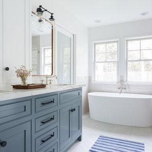 Свежая идея для дизайна: главная ванная комната среднего размера в современном стиле с отдельно стоящей ванной, врезной раковиной, фасадами в стиле шейкер, синими фасадами, угловым душем, бежевой плиткой, белыми стенами, душем с распашными дверями, бежевой столешницей, полом из керамогранита, мраморной столешницей, белым полом и плиткой кабанчик - отличное фото интерьера