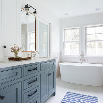 Inspiration for a mid-sized contemporary master beige tile and subway tile porcelain tile and white floor bathroom remodel in Los Angeles with an undermount sink, shaker cabinets, blue cabinets, white walls, a hinged shower door, beige countertops and marble countertops