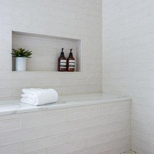 Стильный дизайн: главная ванная комната среднего размера в современном стиле с отдельно стоящей ванной, врезной раковиной, фасадами в стиле шейкер, синими фасадами, угловым душем, бежевой плиткой, плиткой кабанчик, белыми стенами, полом из керамогранита, мраморной столешницей, белым полом и душем с распашными дверями - последний тренд
