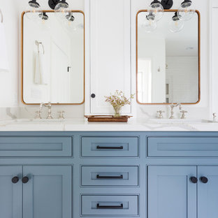 Design ideas for a medium sized contemporary ensuite bathroom in Los Angeles with a freestanding bath, a submerged sink, shaker cabinets, blue cabinets, a corner shower, beige tiles, metro tiles, white walls, porcelain flooring, marble worktops, white floors and a hinged door.