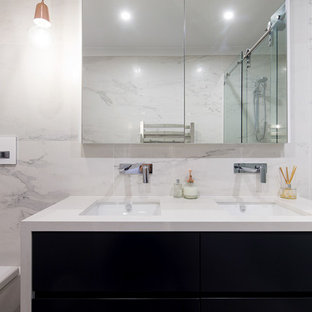 Mid-sized contemporary master bathroom in Sydney with flat-panel cabinets, black cabinets, a wall-mount toilet, gray tile, ceramic tile, multi-coloured walls, ceramic floors, an undermount sink and granite benchtops.