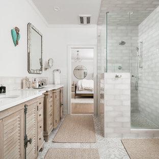 Modelo de cuarto de baño principal, campestre, grande, con armarios con puertas mallorquinas, puertas de armario de madera clara, ducha esquinera, baldosas y/o azulejos beige, paredes blancas, lavabo bajoencimera, suelo gris, ducha con puerta con bisagras y encimeras blancas