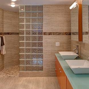 Пример оригинального дизайна: главная ванная комната среднего размера в стиле модернизм с плоскими фасадами, фасадами цвета дерева среднего тона, накладной ванной, бежевой плиткой, бежевыми стенами, полом из известняка, настольной раковиной, стеклянной столешницей и плиткой из известняка
