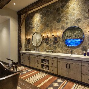 Idee per una stanza da bagno stile rurale con lavabo integrato, ante lisce, ante beige, top in cemento, vasca freestanding, doccia doppia, WC monopezzo, piastrelle marroni, piastrelle in pietra, pareti beige e pavimento in gres porcellanato
