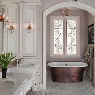 サンフランシスコの広いヴィクトリアン調のおしゃれなマスターバスルーム (アンダーカウンター洗面器、落し込みパネル扉のキャビネット、白いキャビネット、置き型浴槽、紫の壁、大理石の床、グレーの床、白い洗面カウンター) の写真