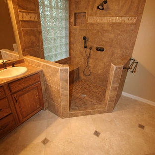 Inspiration for a mid-sized timeless master beige tile, brown tile and ceramic tile ceramic floor and beige floor corner shower remodel in Dallas with raised-panel cabinets, medium tone wood cabinets, beige walls, a drop-in sink, laminate countertops and a hinged shower door