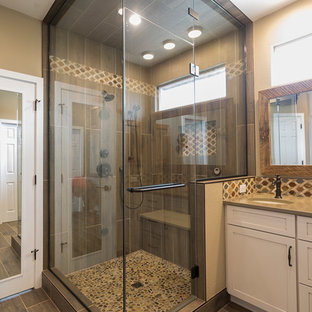 Example of a mid-sized mountain style master brown tile and porcelain tile porcelain tile and brown floor alcove shower design in Denver with shaker cabinets, beige cabinets, beige walls, an undermount sink, quartz countertops, a hinged shower door and brown countertops