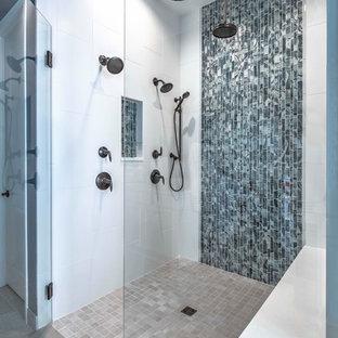 Foto på ett mellanstort funkis en-suite badrum, med en dusch i en alkov, blå kakel, glaskakel, blå väggar, beiget golv och dusch med gångjärnsdörr