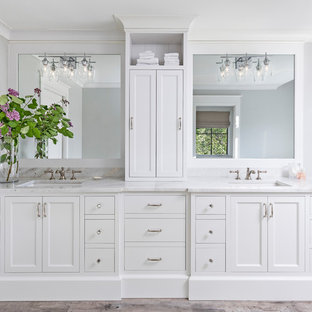 Inspiration for a large beach style master white tile and subway tile porcelain floor and brown floor bathroom remodel in Detroit with recessed-panel cabinets, white cabinets, a one-piece toilet, gray walls, a drop-in sink, marble countertops, a hinged shower door and white countertops