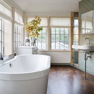 Inspiration for a medium sized mediterranean ensuite bathroom in Dallas with a freestanding bath, a walk-in shower, a one-piece toilet, ceramic tiles, white walls, medium hardwood flooring, a pedestal sink, brown floors, a hinged door and blue tiles.