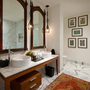 Modelo de cuarto de baño ecléctico, grande, con lavabo sobreencimera, puertas de armario de madera oscura, encimera de mármol, bañera exenta, sanitario de una pieza, losas de piedra, paredes blancas, suelo de mármol y armarios con paneles lisos