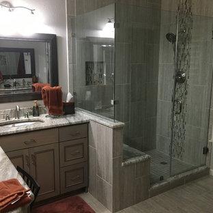 Immagine di una stanza da bagno padronale minimal di medie dimensioni con ante con riquadro incassato, ante grigie, doccia ad angolo, piastrelle grigie, piastrelle in gres porcellanato, pareti grigie, pavimento in gres porcellanato, lavabo sottopiano, top in marmo, pavimento grigio e porta doccia a battente