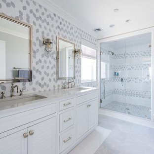 Alcove shower - mid-sized coastal master multicolored tile and ceramic tile marble floor and gray floor alcove shower idea in New York with louvered cabinets, white cabinets, a one-piece toilet, white walls, an undermount sink, quartzite countertops, a hinged shower door and white countertops