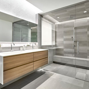 Modelo de cuarto de baño principal, actual, grande, con armarios con paneles lisos, puertas de armario de madera clara, baldosas y/o azulejos grises, baldosas y/o azulejos de porcelana, suelo de baldosas de porcelana, encimera de acrílico, suelo gris, ducha doble, lavabo integrado y ducha abierta