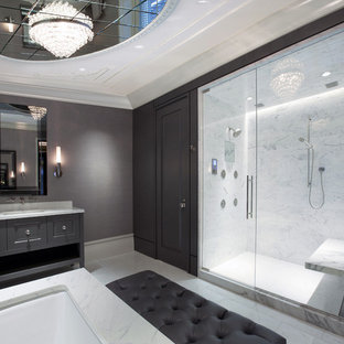 Inspiration for an expansive contemporary ensuite bathroom in Chicago with a submerged sink, raised-panel cabinets, grey cabinets, an alcove shower, white tiles, marble worktops, a submerged bath, grey walls, marble flooring, marble tiles and a shower bench.