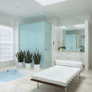 Modelo de cuarto de baño actual con armarios con paneles lisos, puertas de armario blancas, jacuzzi y ducha empotrada