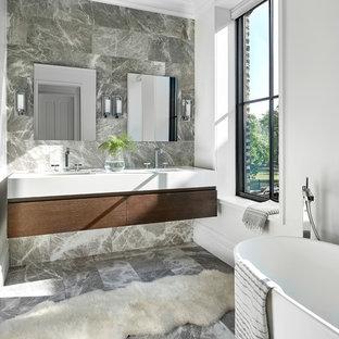 Inredning av ett klassiskt mellanstort en-suite badrum, med släta luckor, ett fristående badkar, grå kakel, stenkakel, ett undermonterad handfat, bänkskiva i akrylsten, grått golv, skåp i mörkt trä och vita väggar